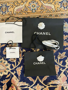 Four Chanel Black paper shopping bags With White Camelia And Ribbon
