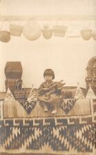 NATIVE AMERICAN CHILD SEATED ON BLANKET, OTHER ARTIFACTS REAL PHOTO PC c 1910-20
