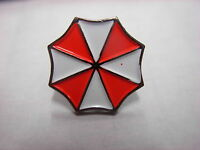 Resident Evil Umbrella novelty pin badge. Red and white lapel pin. Overview.