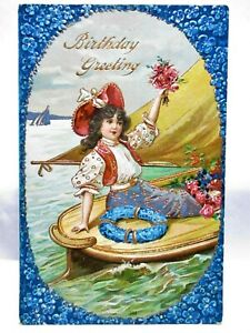 1910 POSTCARD BIRTHDAY GREETINGS, GIRL ON BOAT HOLDING UP FLOWERS, GOLD TRIM