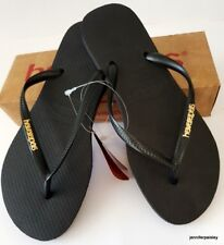 20e82cbc8c37 Havaianas Womens Slim Thongs With Gold Logo in Black Thongs Best Sellers  3940