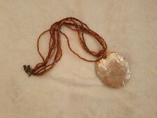 statement brown seed bead and mother of pearl central pendant necklace