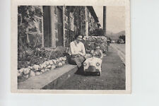 Postcard size photo of young boy in pedal car with his mother outside row of cot