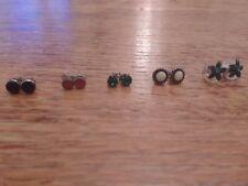 FIVE SETS of stud earrings: black; red; emerald; white; green stone flower
