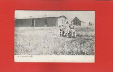 Pioneer Days. Lady seated with girl and dog beside her, sod house behind
