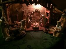 10 piece figurine, 14' crèche with hay bales, wood piles, and pottery. Light inc