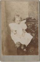 Antique CABINET PHOTOGRAPH of a grumpy faced BABY CHILD INFANT Taken in a house.