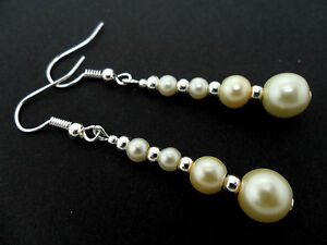 A PAIR OF DANGLY IVORY GLASS PEARL  SILVER PLATED EARRINGS.