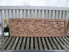 A LARGE HAND CARVED HARDWOOD PANEL, DEPICTING BARBARIC TRIBAL WARRIORS IN BATTLE
