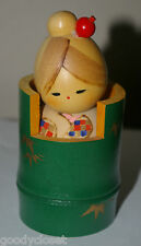 KOKESHI GIRL DOLL SIGNED IN BRIGHT GREEN DRUM/CONTAINER AND RED HAIR PIN