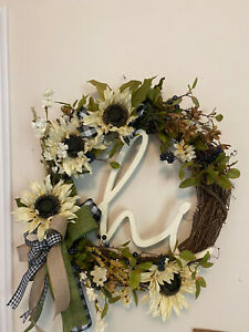 "Farmhouse wreath on a grapevine with cream colored flowers/ ""hi"" sign and a bow"