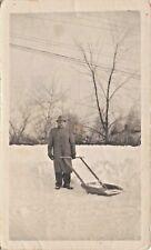 MAN USING SLED TYPE SNOW SHOVEL PHOTO