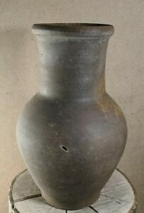 Antique tall brown clay pot in traditional Ukrainian rustic style