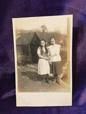 RPPC of two shy girls (sisters?) standing next to a house. One looks suspicious.