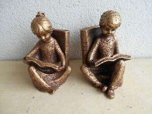 Zwei Buchstützen aus Bronze: Lesendes Mädchen und lesender Junge.