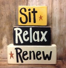 Sit Relax Renew sign stacking wood blocks inspirational quote saying phrase