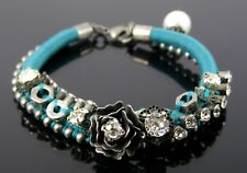 TURQUOISE CORD & ANTIQUE SILVER BRACELET WITH CRYSTALS, ROSE & CHARMS.