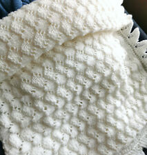 A stunning white hand knit scallop edged Heritage Baby shawl.