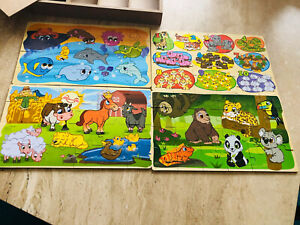 Four wooden animal puzzles in a wooden box