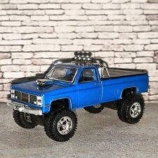 GREENLIGHT CUSTOM LIFTED 1:64 1985 GMC HIGH SIERRA 2500 WITH REAL RIDERS
