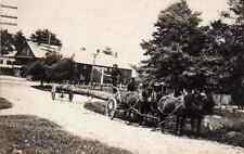 Logging or telephone poll, horse drawn wagon in town, real photo postcard