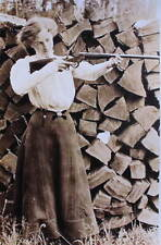 Old Fashioned Woman with Rifle Wood Pile.