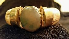 womens heavy ivory colored and brass w/ purple-ish/green stone braclet