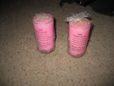 Two pink and gold love candles
