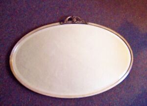 Antique oval mirror silvered bronze with urn top 27 1/2 x 18 in beveled edge