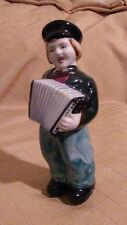 Vintage hand painted porcelain boy playing his accordion.