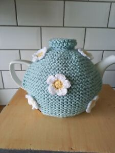 Hand knitted tea cosy medium.Duck egg blue decorated with white crochet flowers