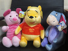 A set of winnie the pooh, piglet and eeyore soft plush toys
