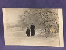 Woman and boy in forest in winter real photo postcard