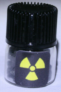 Uranium ore in glass vial with sticker. Pitchblende. Active. Geiger counter.