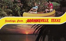 Greetings from Brownsville TX,  Couple in canoe in shorts 1950's, postcard