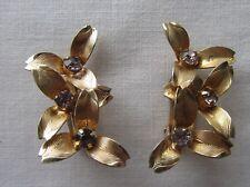 Vintage gold tone clip on flower earrings with purple rhinestones