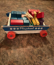 Vintage Playskool pull cart with bright orange wheels and wooden building blocks