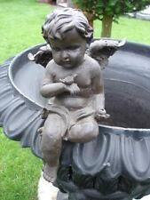 un ange assis avec un oiseau  ,statue en fonte patinée brun rouillé