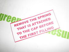 'Remove the spring that is attached to the cap before the first filling' Sticker