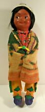 SKOOKUM RIGHT LOOKING DOLL. WRAPPED IN BLANKET, BEADED NECKLACE. MOCCASINS