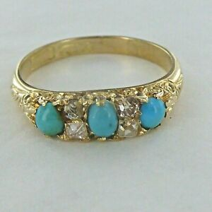 A GOOD ANTIQUE CABOCHON THREE STONE TURQUOISE AND DIAMOND RING.