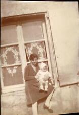 snapshot femme avec bébé devant une fenêtre mode layette robe bas blancs