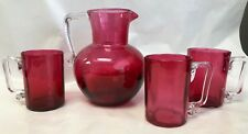 HAND BLOWN CRANBERRY GLASS PITCHER AND 3 MUGS APPLIED HANDLES