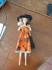 barbie in a halloween dress with witch hat and broom
