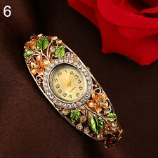 LADIES CRYSTAL QUARTZ CUFF WATCH WITH A MASS OF COLOURED FLOWERS SENT IN A GIFT
