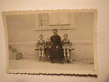 Frau & 3 Kinder - Mädchen & Jungen sitzen auf einer Bank vor einem Haus / Foto