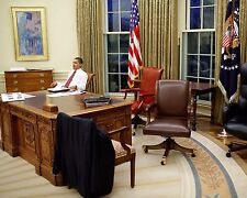 President Barack Obama tries out desk chairs in the Oval Office Photo Print