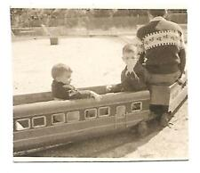 REAL PHOTO-BLACK AND WHITE 1950'S-TWO CHILDREN IN A TOY TRAIN-2 1/2 X 2 3/4 EX