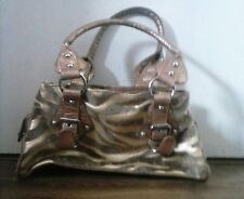 small gold and brown zebra stripe handbag with fur detail. several compartments