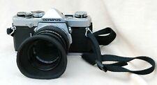 Olympus OM-1 35mm SLR film camera with 50mm Olympus lens.